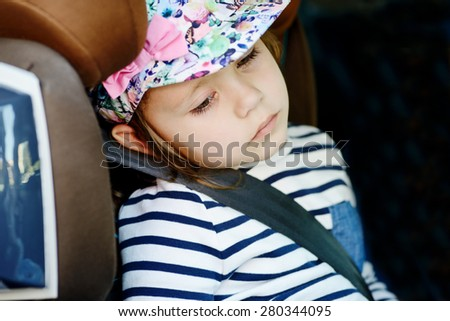 tired little girl in the car seat - stock photo