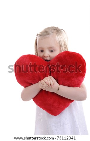 tired little girl wit red heart shaped pillow