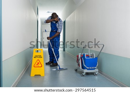 Tired Male Janitor With Cleaning Equipment And Wet Floor Sign In Corridor - stock photo