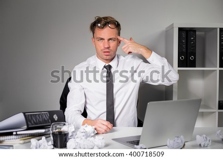Tired man at the office showing gun sign  - stock photo