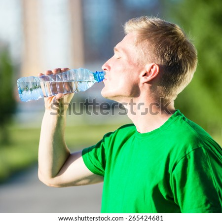 Tired man drinking water from a plastic bottle after fitness time and exercising in city street park at beautiful summer day. Sporty model caucasian ethnicity training outdoor.  - stock photo