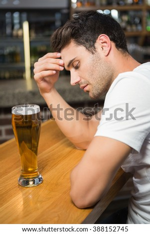 Tired man having a beer in a pub