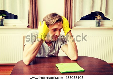 Tired man in yellow gloves sitting behind the desk