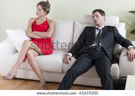Tired man on sofa, disappointed woman ready to go out