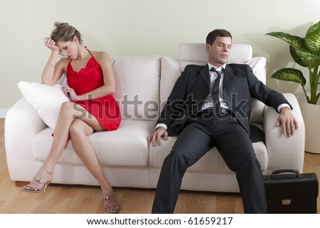 Tired man on sofa, disappointed woman ready to go out - stock photo