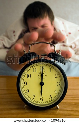 Tired man reaching for his alarm clock at 6:00 in the morning