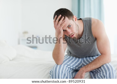 Tired man sitting on his bed while looking at the camera