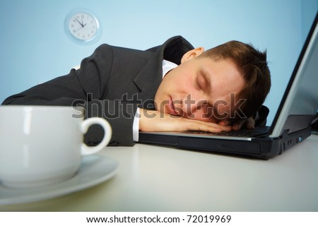 Tired man sleeping at work with computer. Office people sometimes dozing on workplace. - stock photo