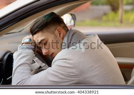 tired man sleeping behind the wheel of a car - stock photo