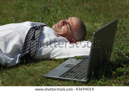 Tired man sleeping in a field near his laptop. - stock photo