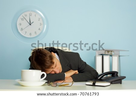 tired man sleeping on a table next to mug and phone - stock photo