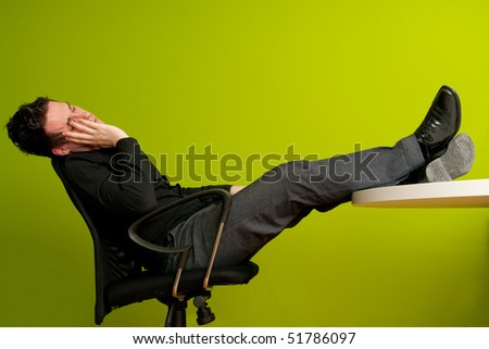Tired man sleeping on chair in office with his legs on the table