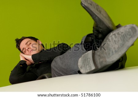 Tired man sleeping on chair in office with his legs on the table - stock photo