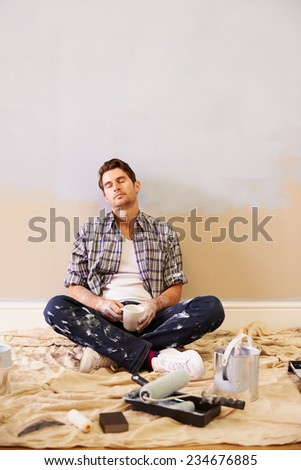 Tired Man Taking A Break Whilst Decorating Room - stock photo