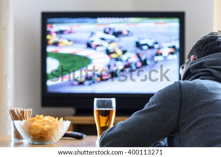 Tired man watching TV (formula one race) in living room with alcohol and snacks - stock photo - stock photo