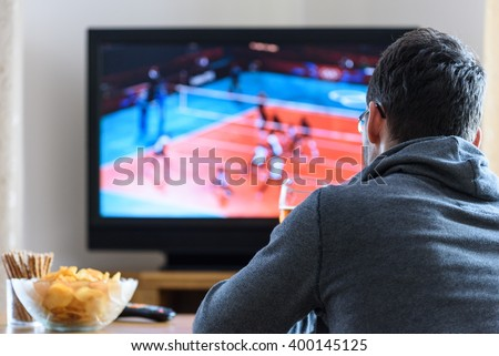 Tired man watching TV (volleyball match) in living room with alcohol and snacks - stock photo