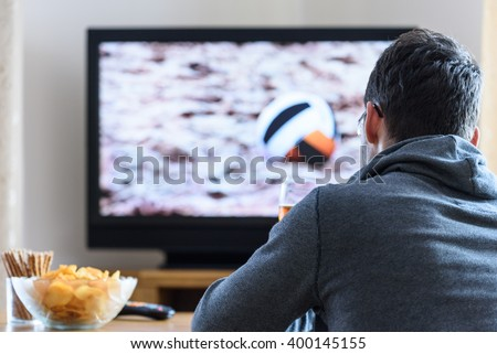 Tired man watching TV (volleyball match) in living room with alcohol and snacks - stock photo - stock photo