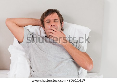 Tired man yawning in his bedroom