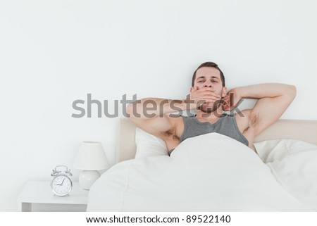 Tired man yawning while waking up in his bedroom - stock photo