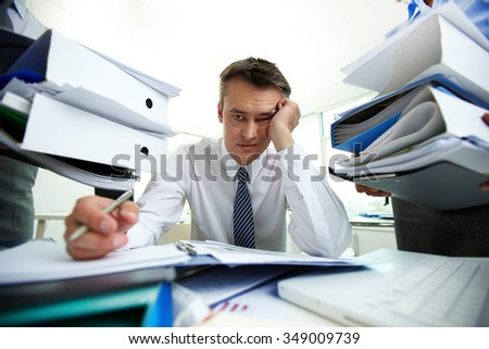 Tired manager have so many paperwork in the office - stock photo
