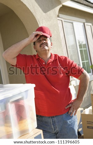 Tired middle aged delivery man in front of moving house