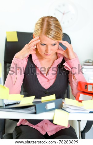 Tired modern business woman sitting at workplace overwhelmed with sticky reminder notes - stock photo
