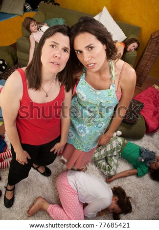 Tired mom and babysitter among sleeping liitle girls - stock photo