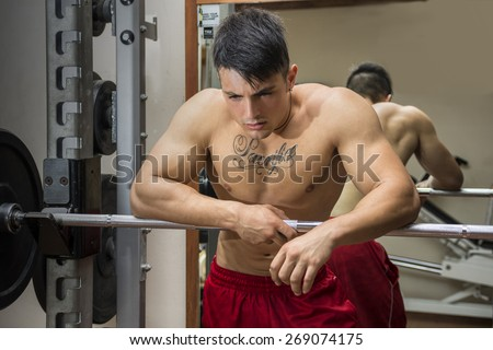 Tired muscular shirtless young male bodybuilder resting on barbell between workouts in gym - stock photo