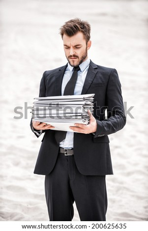 Tired of paperwork. Frustrated young businessman holding stack of paperwork while standing on sand in desert - stock photo