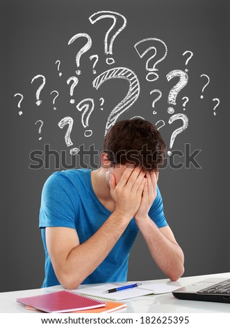 Tired of studying. confused young man covering his head while sitting. with question mark on top of him - stock photo
