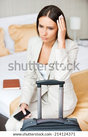 Tired of traveling. Depressed young businesswoman in formalwear holding head in hand while sitting on the bed in hotel room  - stock photo