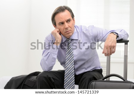 Tired of traveling. Portrait of a thoughtful senior businessman sitting in a sofa at the hotel room and holding his hand on the suitcase - stock photo