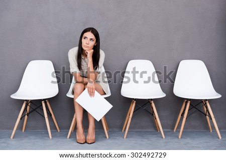 Tired of waiting. Bored young businesswoman holding paper and looking away while sitting on chair against grey background - stock photo