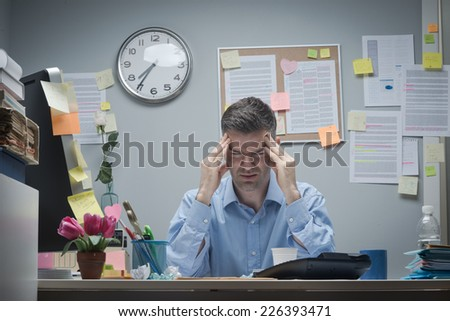 Tired office worker at desk with headache touching his temples. - stock photo