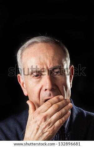 Tired old man yawning on black background - stock photo