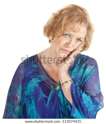 Tired older woman in blue with hand on cheek - stock photo