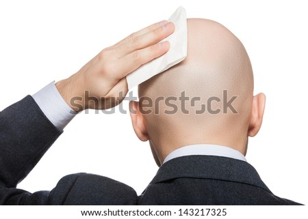 Tired or upset businessman wiping or drying bald sweat head with handkerchief or tissue - stock photo