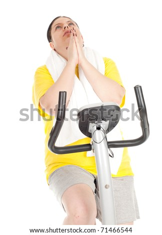 tired overweight, fat woman in yellow shirt on stationary fitness bicycle - stock photo