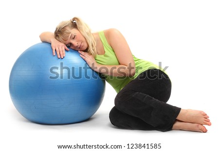Tired overweight woman resting on a blue ball.