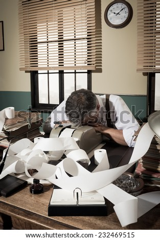 Tired overworked accountant sleeping on his messy desk, 1950s style office. - stock photo