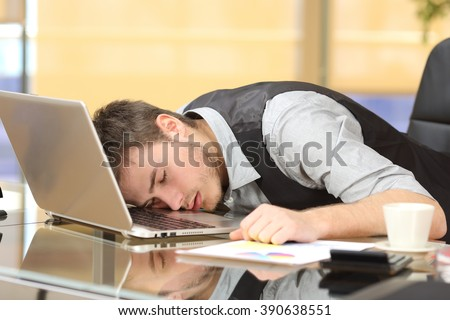 Tired overworked businessman sleeping over a laptop in a desk at job in his office - stock photo