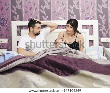 Tired parents with newborn in midnight. - stock photo