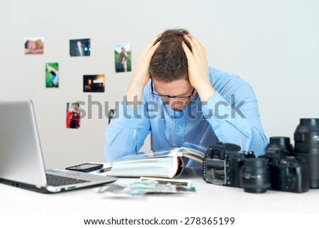 Tired photographer working at his workplace. - stock photo