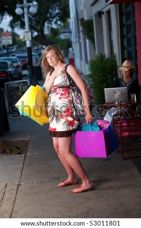 Tired pregnant woman shopping with colorful bags - stock photo