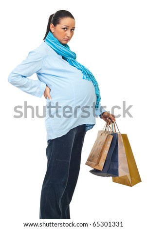 Tired pregnant woman with backache holding shopping bags isolated on white background - stock photo