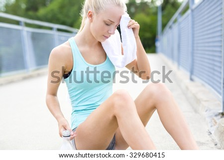 Tired runner sits on the ground and rests after running - stock photo