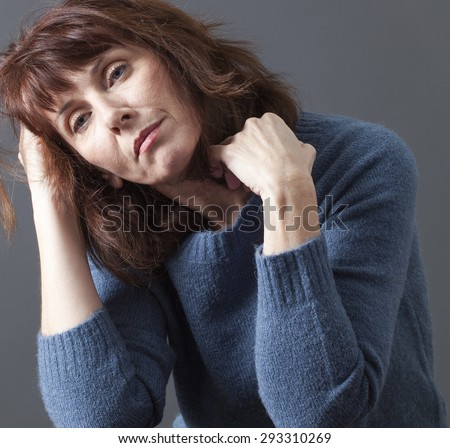 tired 50's woman holding her head and hair for depression, loss or fatigue due to menopause - stock photo