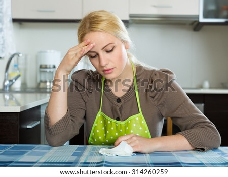 Tired sad blonde young woman sitting at kitchen