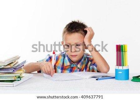 Tired school boy doing homework - stock photo