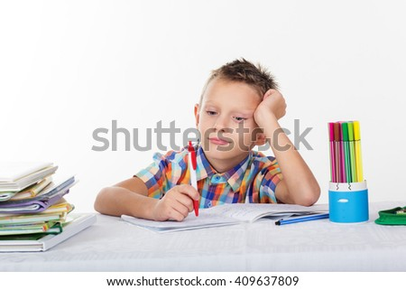 Tired school boy with sad face is doing lessons - stock photo